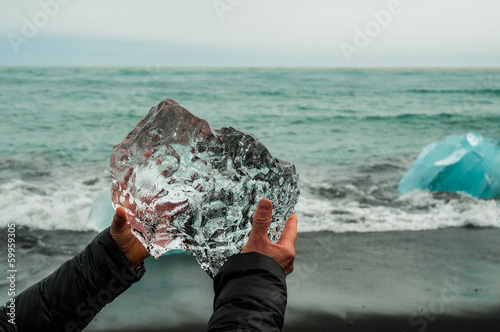 Hands holding a block of pristine glacier ice