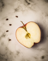 Apple with seeds on  marble surface