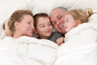 Happy young family cuddling together in bed