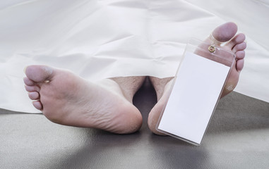 feet of a deceased man with a blank toe tag