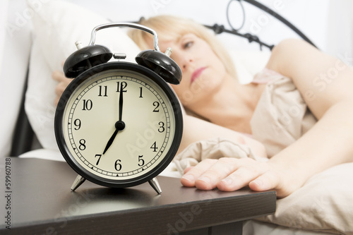 Wake Up Time: Middle Age Woman Reaching for Alarm Clock