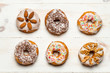 Six colorful donuts on old wooden table