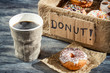Closeup of hot coffee and box with donuts