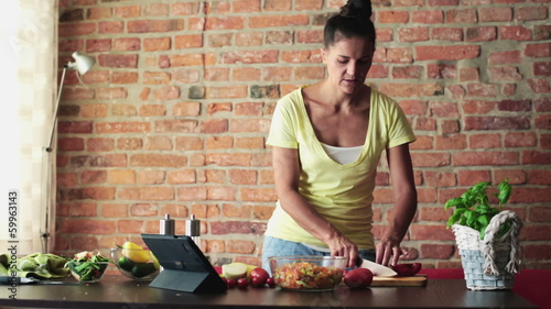 Young woman preparing salad and checking recipe on tablet comput