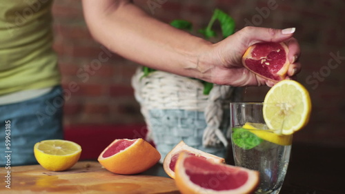 Woman hands squeeze grapefruit into glass, steadicam shot
