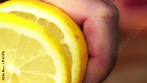 Woman hands cut lemon into slices, closeup