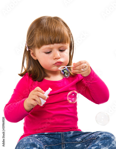 Happy little girl blowing bubbles isolated on white