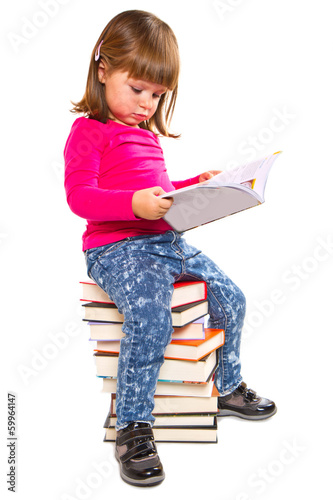 Little girl sitting on stack of books