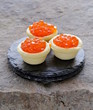 gourmet tartlets with red caviar on a stone plate