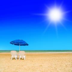 Pair of sun loungers and a beach umbrella on a deserted beach