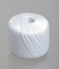 White spool of  thread on studio grey background