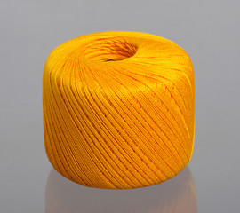 Orange spool of yarn on studio grey background
