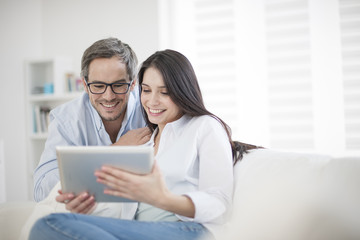 Cheerful couple using digital tablet at home