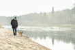 Man walking with dog near the river
