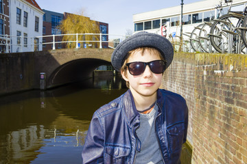 Cute kid with sunglasses and hat in an urban environment