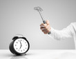 Hand holding hammer over alarm clock