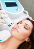 Fototapety Woman getting laser face treatment in medical spa center