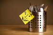 Post-it note with smiley face sticked on a cutlery case