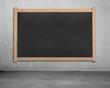 Blank chalk board on concrete wall