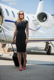 Wealthy Woman With Luggage Walking Against Private Jet poster