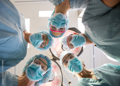 Medical Team Wearing Masks And Scrubs In Operation Room
