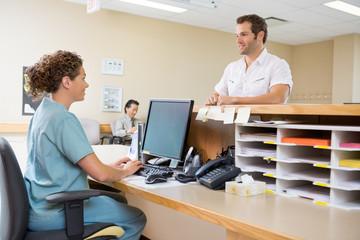 Nurse And Patient Conversing At Reception Desk