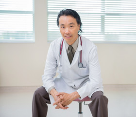 Doctor Sitting At Hospital Room With Patient In Background