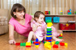 mother and her daughter play with toys at home interior
