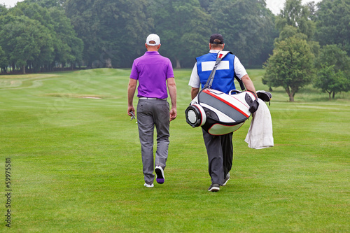 Golfer and caddy walking up a fairway