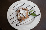 Top view of piece of apple strudel with mint and chocolate
