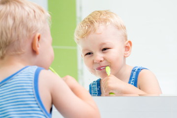 child boy brushing teeth in bathroom