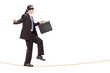 Blindfolded young businessman walking on rope