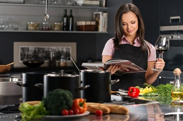 Cheerful young woman in apron on modern kitchen with cookbook