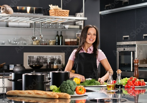 Cheerful young woman in apron on modern kitchen