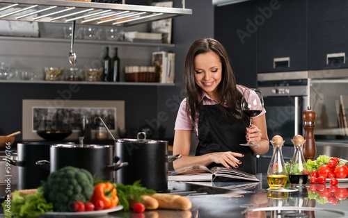 Cheerful young woman in apron on modern kitchen with cookbook an