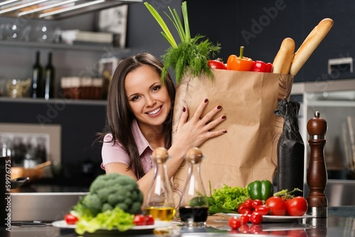 Young woman with grocery bag full of  vegetables