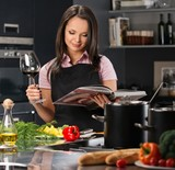Cheerful young woman in apron on modern kitchen with cookbookan