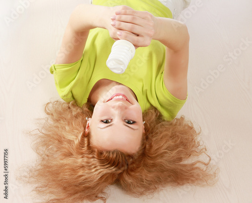 A young woman with an energy-saving bulb, lying on the floor.