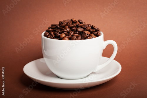Coffee beans in cup on brown background