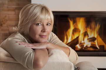 Portrait of adult woman near fireplace