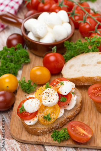 ciabatta with mozzarella and colorful cherry tomatoes on board
