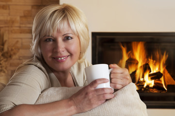 Woman enjoying hot drink by home fireplace