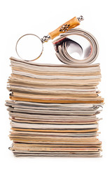 pile of newspapers and magnifying glass