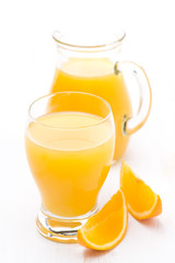 glass and jug of orange juice and fresh orange slices