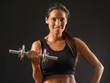 Smiling woman lifting a dumbbell