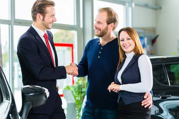 Verkäufer und Kunden mit Auto im Autohaus