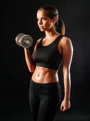 Sexy woman lifting a dumbbell