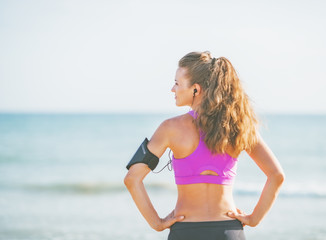 Fitness young woman standing on beach and looking on copy space