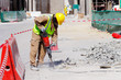 A laborer uses a jackhammer to break up a concrete pavement - 59983594