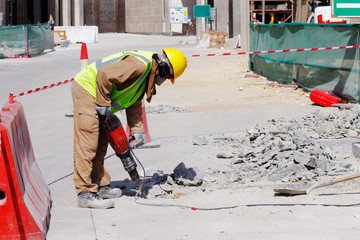 A laborer uses a jackhammer to break up a concrete pavement